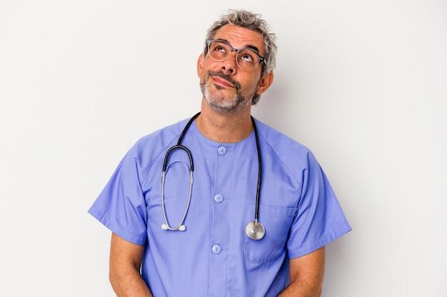目標と目的を達成することを夢見ている白い背景に分離された中年看護師白人男性
