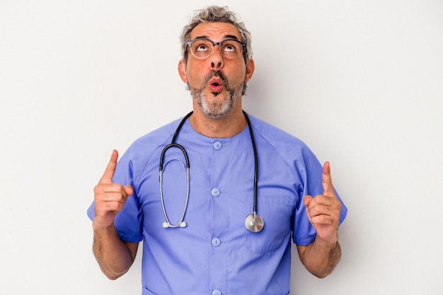 Middle age nurse caucasian man isolated on white background  pointing upside with opened mouth.