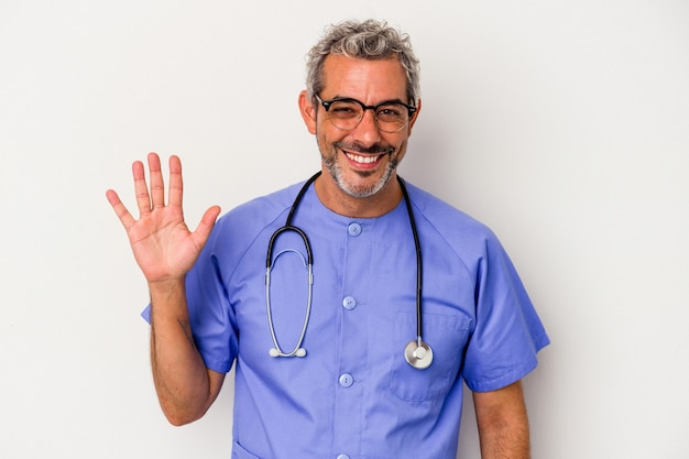 Middle age nurse caucasian man isolated on white background  smiling cheerful showing number five with fingers.