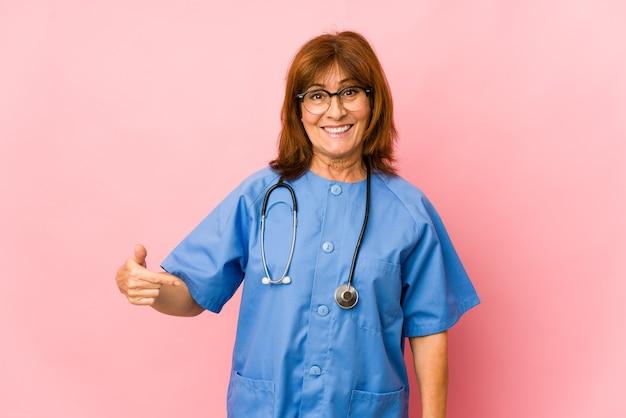 シャツのコピースペースを手で指している中年看護師の女性孤立した人、誇りと自信