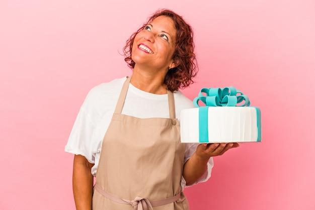 目標と目的を達成することを夢見てピンクの背景に分離されたケーキを保持している中年のペストリーラテン女性