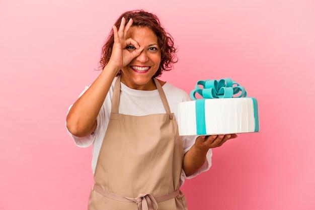 ピンクの背景に分離されたケーキを保持している中年のペストリーラテン女性は、目に大丈夫なジェスチャーを維持して興奮しました。