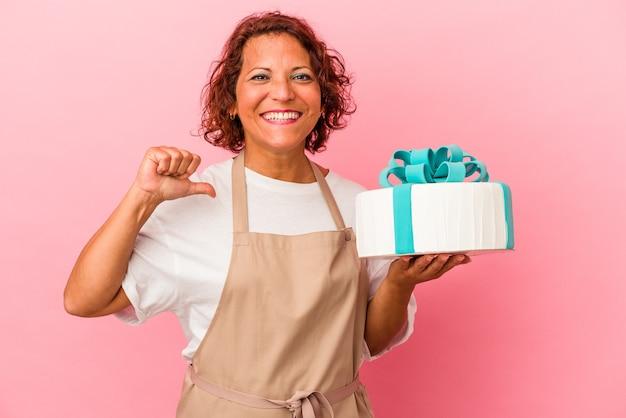 ピンクの背景に分離されたケーキを保持している中年のペストリーラテン女性は、誇りと自信を感じます。