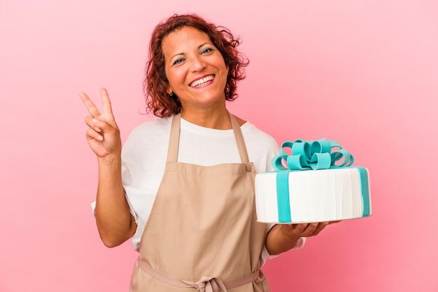 ピンクの背景に分離されたケーキを持っている中年のペストリーラテン女性は、指で平和のシンボルを示して楽しくてのんきです。