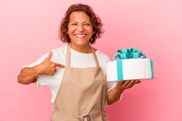 シャツのコピースペースを手で指しているピンクの背景の人に分離されたケーキを保持している中年のペストリーラテン女性、誇りと自信を持って