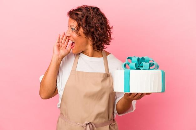 ピンクの背景に分離されたケーキを持って叫び、開いた口の近くで手のひらを保持している中年のペストリーラテン女性。
