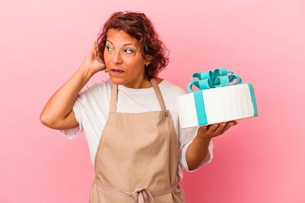 ゴシップを聴こうとしているピンクの背景に分離されたケーキを保持している中年のペストリーラテン女性。
