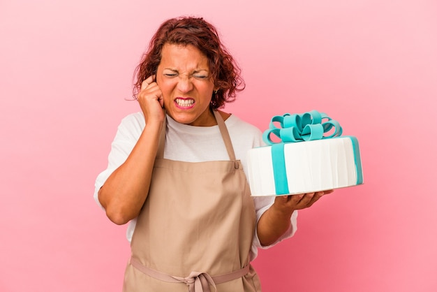 Middle age pastry latin woman holding a cake isolated on pink background covering ears with hands.