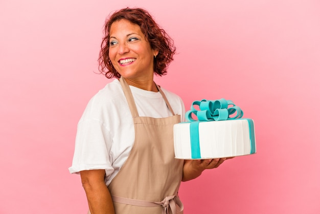 Middle age pastry latin woman holding a cake isolated on pink background looks aside smiling, cheerful and pleasant.