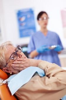 歯科医院の椅子に座って痛みを伴う表情で口に触れる中年患者。歯について非難し、不平を言っている医療病院の年配の女性。