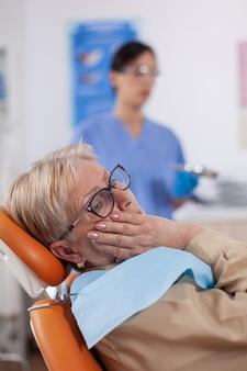 歯科医院の椅子に座って痛みを伴う表情で口に触れる中年患者