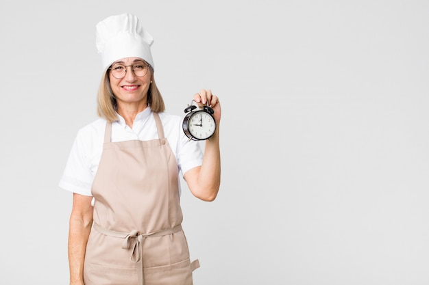 Middle age pretty baker  woman holding an alarm clock