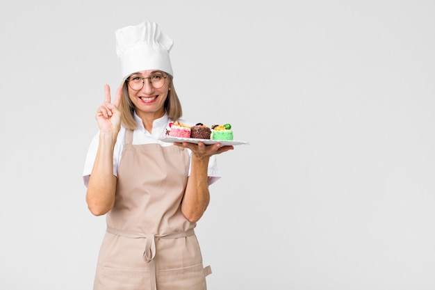 Middle age pretty baker  woman with cakes against copy space wall