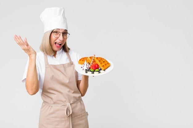 Женщина пекаря среднего возраста милая с вафлями против стены космоса экземпляра