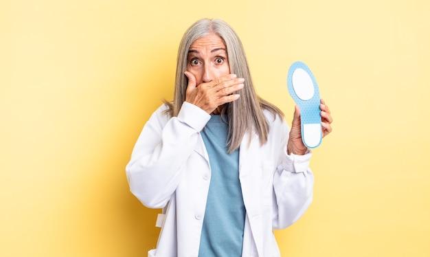ショックを受けた手で口を覆う中年のきれいな女性。足病専門医の概念