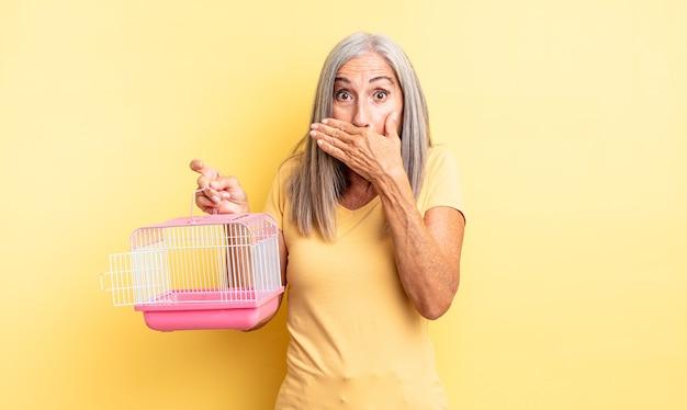 ショックを受けた手で口を覆う中年のきれいな女性。ペットケージまたは刑務所の概念