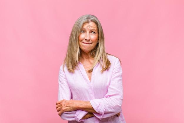 Симпатичная женщина среднего возраста сомневается или думает, кусает губу и чувствует себя неуверенно и нервно, пытаясь скопировать пространство сбоку