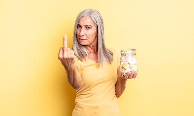 怒り、イライラ、反抗的、攻撃的な中年のきれいな女性。キャンディーボトルのコンセプト