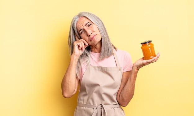Симпатичная женщина среднего возраста чувствует скуку, разочарование и сонливость после утомительного. персиковое варенье