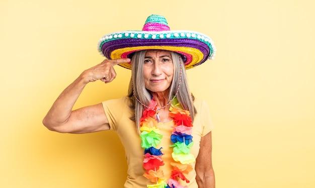중년의 예쁜 여자는 혼란스럽고 의아해하며 당신을 미쳤음을 보여줍니다. 멕시코 파티 개념