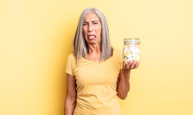 中年のきれいな女性は嫌悪感とイライラを感じ、舌を出します。キャンディーボトルのコンセプト