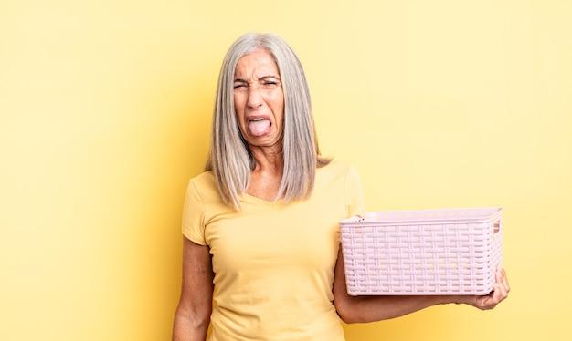 Среднего возраста симпатичная женщина чувствует отвращение и раздражение и вытаскивает язык. концепция пустой корзины