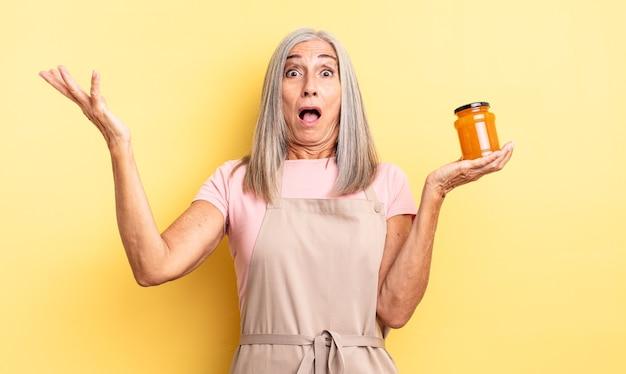 Симпатичная женщина среднего возраста чувствует себя чрезвычайно шокированной и удивленной. персиковое варенье