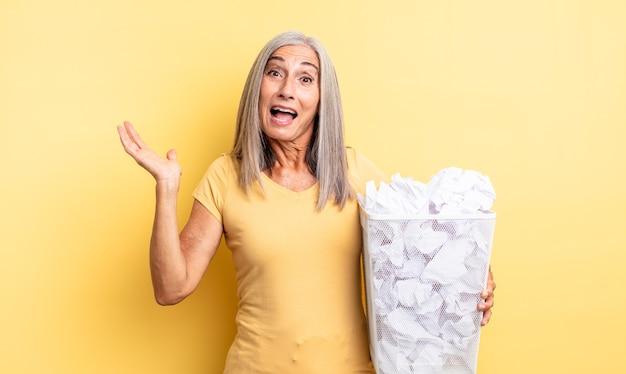 Среднего возраста симпатичная женщина чувствует себя счастливой и удивляется чему-то невероятному. концепция провала бумажных шаров