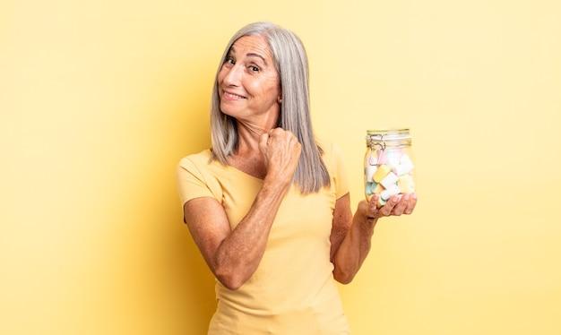 幸せを感じ、挑戦に直面したり、祝ったりする中年のきれいな女性。キャンディーボトルのコンセプト