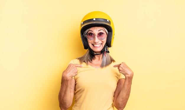 중년의 예쁜 여자는 행복감을 느끼고 흥분하여 자신을 가리키고 있습니다. 오토바이 헬멧 개념