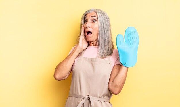 Симпатичная женщина среднего возраста чувствует себя счастливой, взволнованной и удивленной. концепция рукавицы духовки
