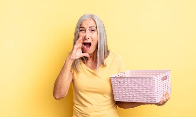 Среднего возраста симпатичная женщина чувствует себя счастливой, громко кричит, прижав руки ко рту. концепция пустой корзины