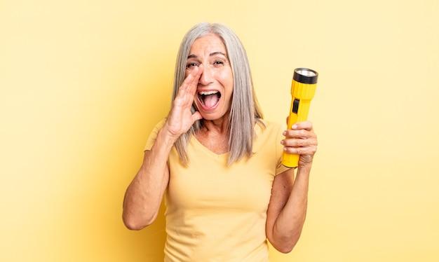 幸せを感じている中年のきれいな女性は、口の横に手で大きな叫び声をあげます。懐中電灯のコンセプト