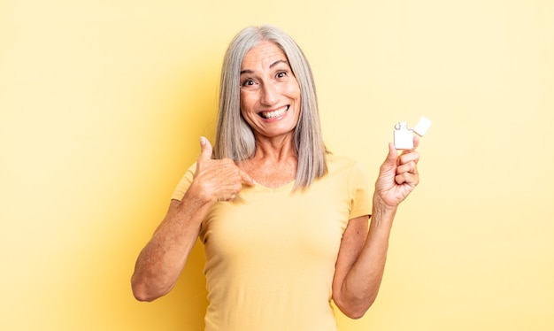 Middle age pretty woman feeling happy and pointing to self with an excited. lighter concept