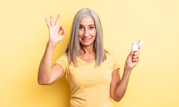 Middle age pretty woman feeling happy, showing approval with okay gesture. lighter concept