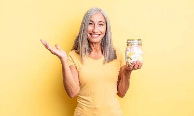 幸せを感じ、解決策やアイデアを実現して驚いた中年のきれいな女性。キャンディーボトルのコンセプト
