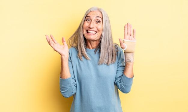 幸せを感じ、解決策やアイデアを実現して驚いた中年のきれいな女性。手の包帯の概念