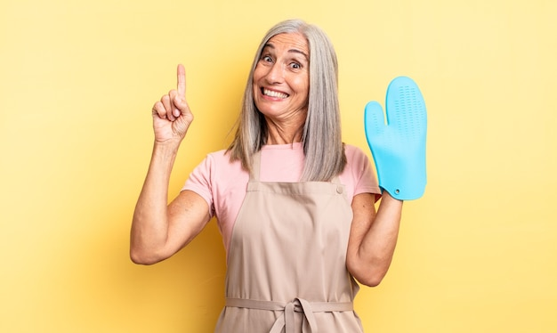 Middle age pretty woman feeling like a happy and excited genius after realizing an idea. oven mitt concept