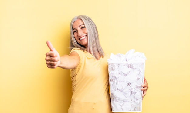 Middle age pretty woman feeling proud,smiling positively with thumbs up. paper balls failure concept