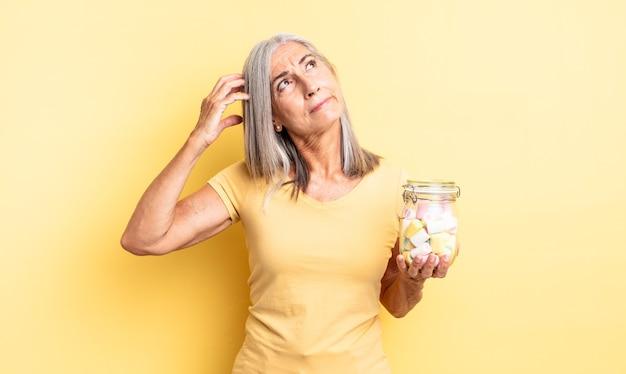 頭をかいて、戸惑い、混乱している中年のきれいな女性。キャンディーボトルのコンセプト