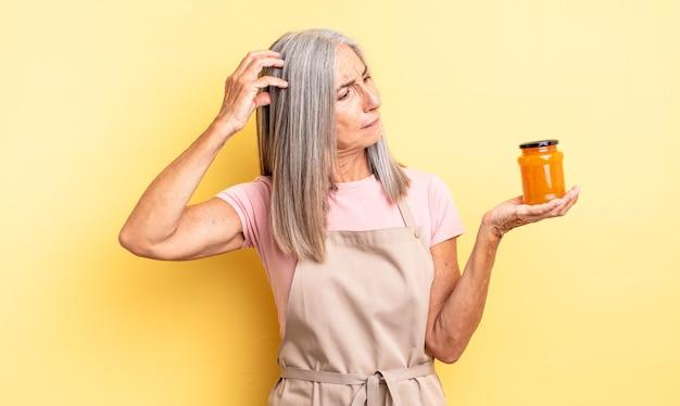 Симпатичная женщина среднего возраста, чувствуя себя озадаченной и растерянной, почесывая голову. персиковое варенье