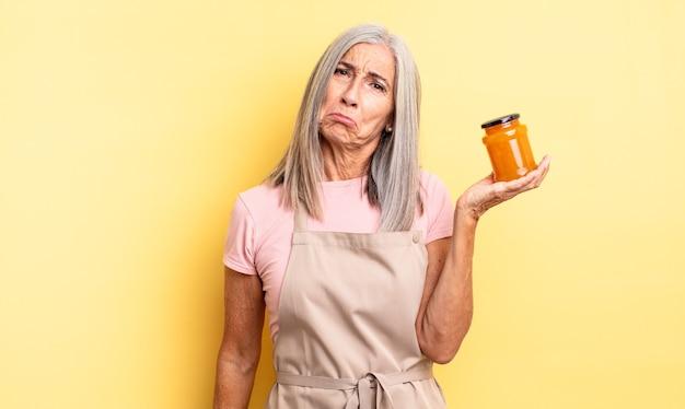 Симпатичная женщина среднего возраста грустит и плаксиво смотрит и плачет. персиковое варенье