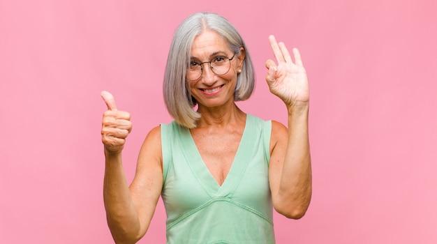 Красивая женщина среднего возраста чувствует себя потрясенной, взволнованной и счастливой, смеется и празднует успех