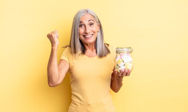 ショックを受け、笑い、成功を祝う中年のきれいな女性。キャンディーボトルのコンセプト