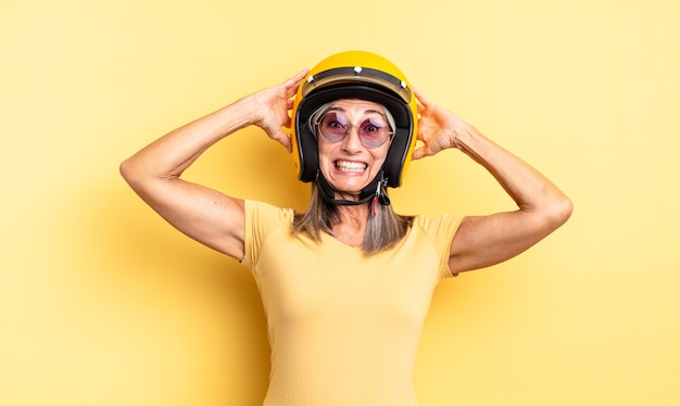 Симпатичная женщина среднего возраста чувствует стресс, тревогу или страх, с руками за голову. концепция мотоциклетного шлема
