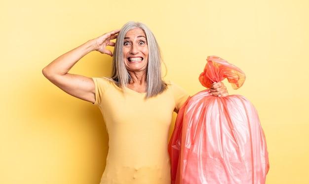중년의 예쁜 여성은 머리에 손을 얹고 스트레스를 받거나 불안해하거나 무서워합니다. 플라스틱 쓰레기 봉투