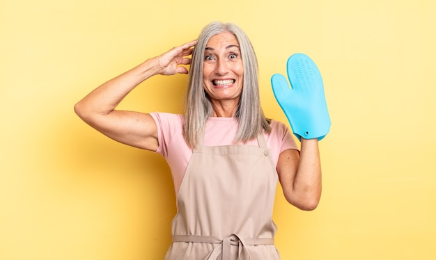 Middle age pretty woman feeling stressed, anxious or scared, with hands on head. oven mitt concept