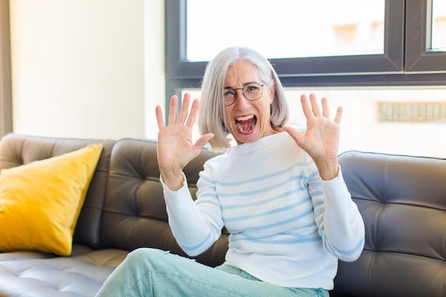 Симпатичная женщина среднего возраста чувствует себя ошеломленной и напуганной, боится чего-то пугающего, с раскинутыми руками говорит: «держись подальше»