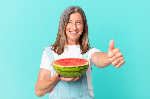 Middle age pretty woman holding a watermelon slice
