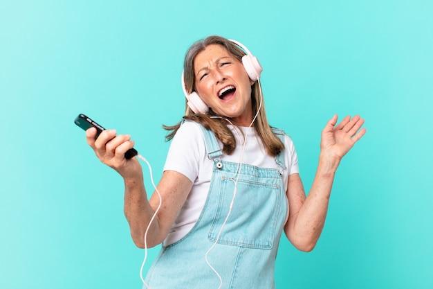 중년 예쁜 여자는 헤드폰으로 듣는 음악